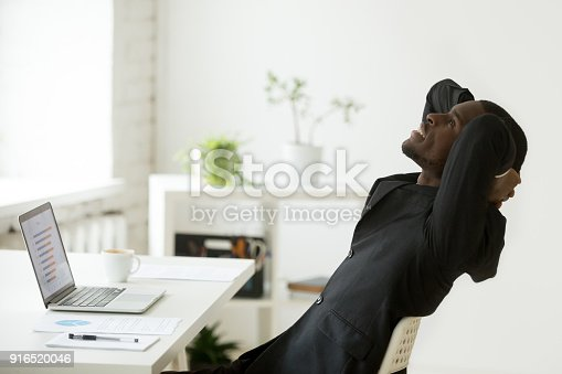 istock Satisfied relaxed african-american businessman in suit feeling happy at work 916520046