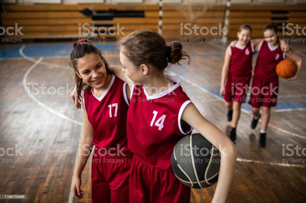 Satisfied female teenagers leaving basketball field in school gym...