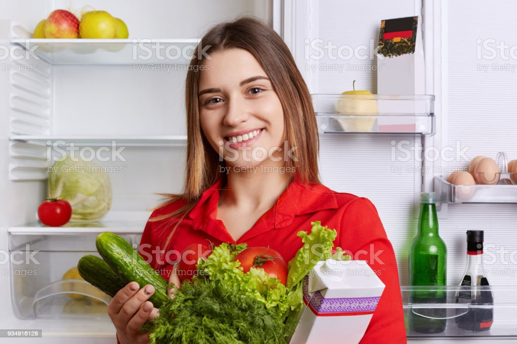 Satisfied woman holds fresh vegetables and milk, going to put them in refridgerator, has broad smile and happy expression, being vegeterian, eats only healthy food. People and nutrition concept stock photo
