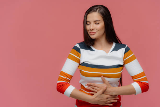 Satisfied woman keeps hands on belly, feels replete after delicious supper, has full stomach, long hair, appealing appearance, wears jumper, models on pink wall. Lady finds out about pregnancy Satisfied woman keeps hands on belly, feels replete after delicious supper, has full stomach, long hair, appealing appearance, wears jumper, models on pink wall. Lady finds out about pregnancy full stock pictures, royalty-free photos & images
