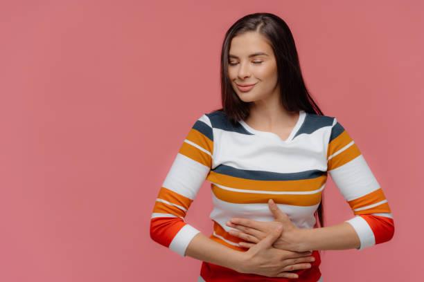 a mulher satisfeita mantem as mãos na barriga, sente-se repleta após a ceia deliciosa, tem o estômago cheio, cabelo longo, aparência atraente, desgasta o jumper, modelos na parede cor-de-rosa. a senhora descobre sobre a gravidez - estômago - fotografias e filmes do acervo