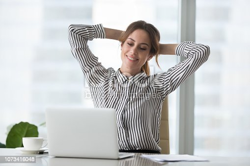 istock Satisfied woman relaxing with hands over head. 1073416048