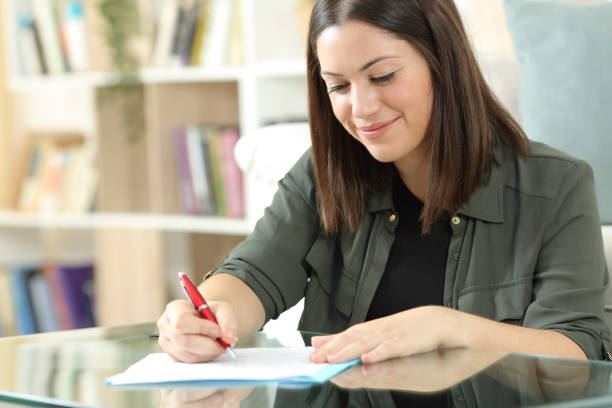 Satisfied woman signing document at home stock photo