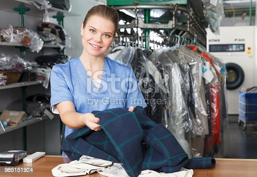 istock Satisfied worker with clothes after dry cleaning 985151924
