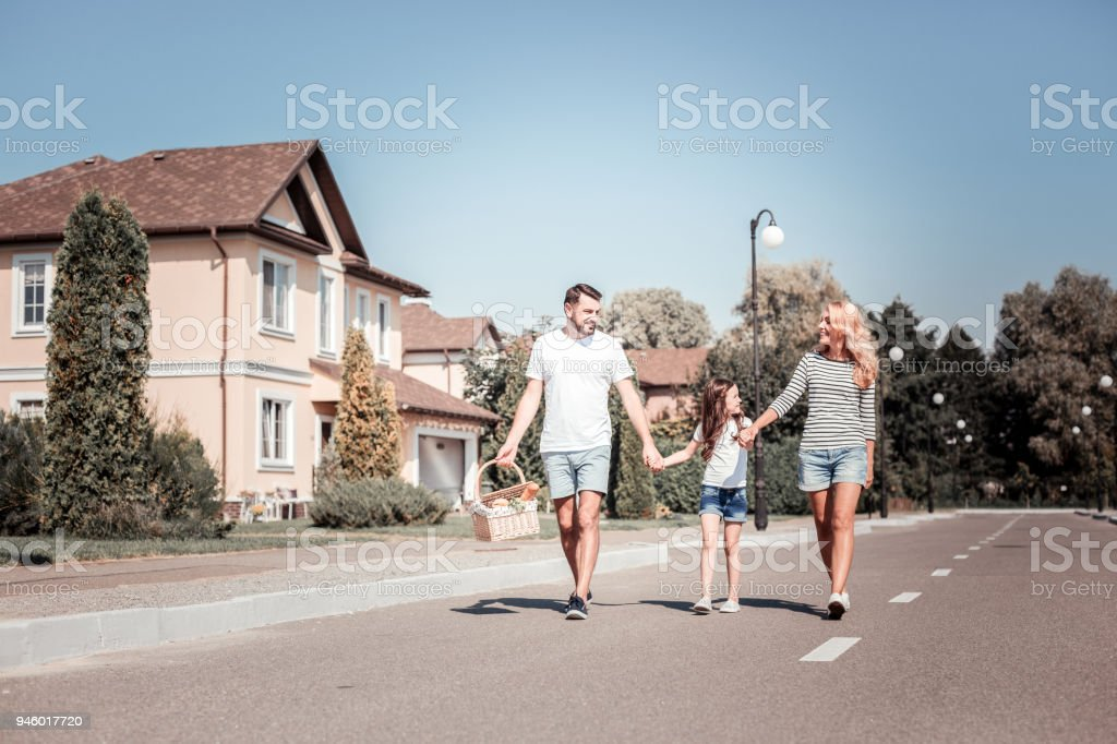 Satisfied young family walking and bringing product basket. stock photo