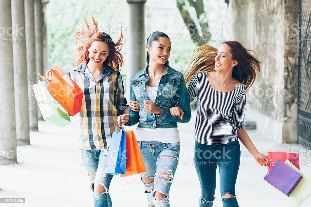 Satisfied young friends holding colored purcheses stock photo