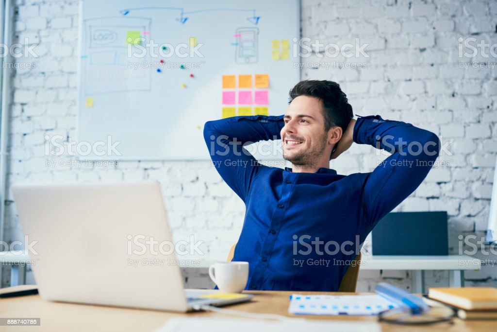 Satisfied young man in office looking away stock photo