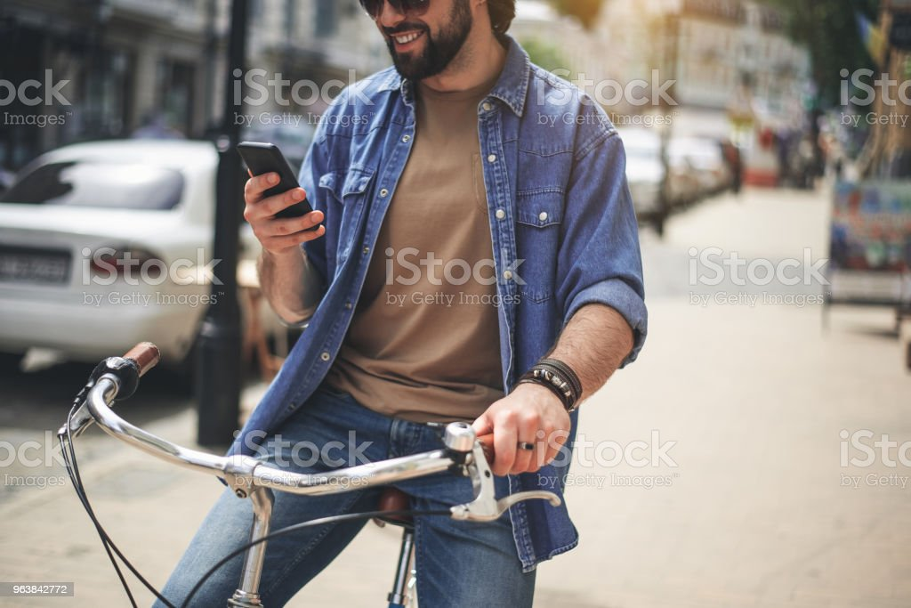 Satisfied young man taking seat on bicycle with phone - Royalty-free Adult Stock Photo
