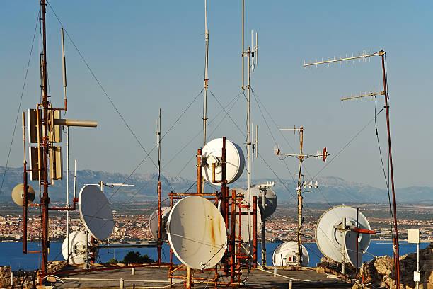 sattelite albero e piatti su un tetto - emissione radio televisiva foto e immagini stock