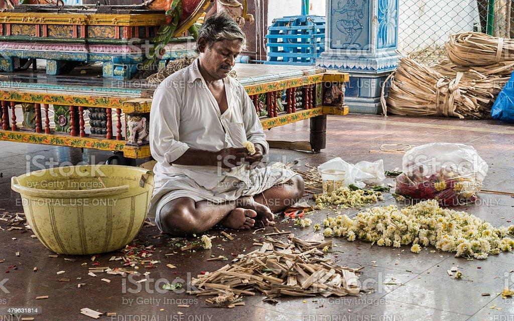 Sattharar making a floral garment in a Hindu temple. stock photo