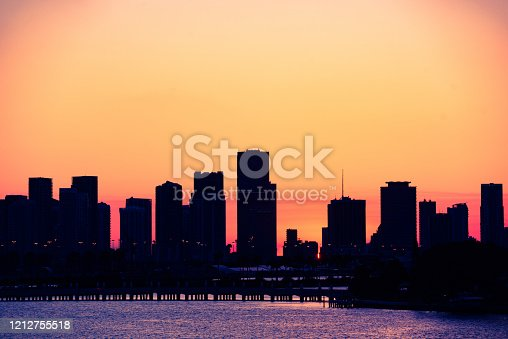 This is a color photograph of a orange sunset sky creating a silhouette of the Downtown Miami buildings along Biscayne Boulevard seen behind the bridge to Star Island in Miami Beach, Florida.