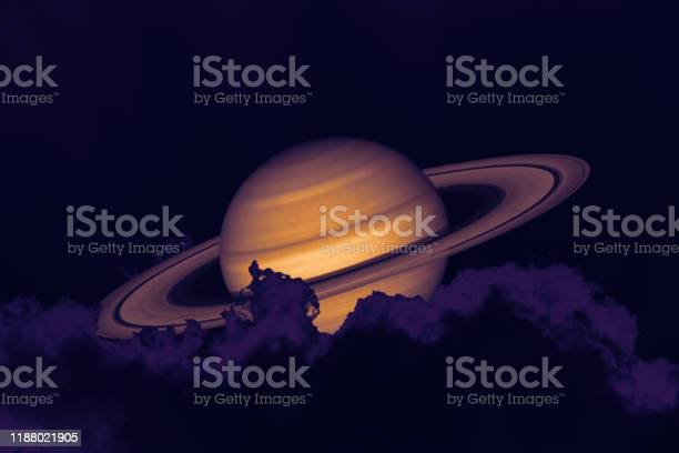 Photo of Saturn on night sky back silhouette mountain and heap cloud