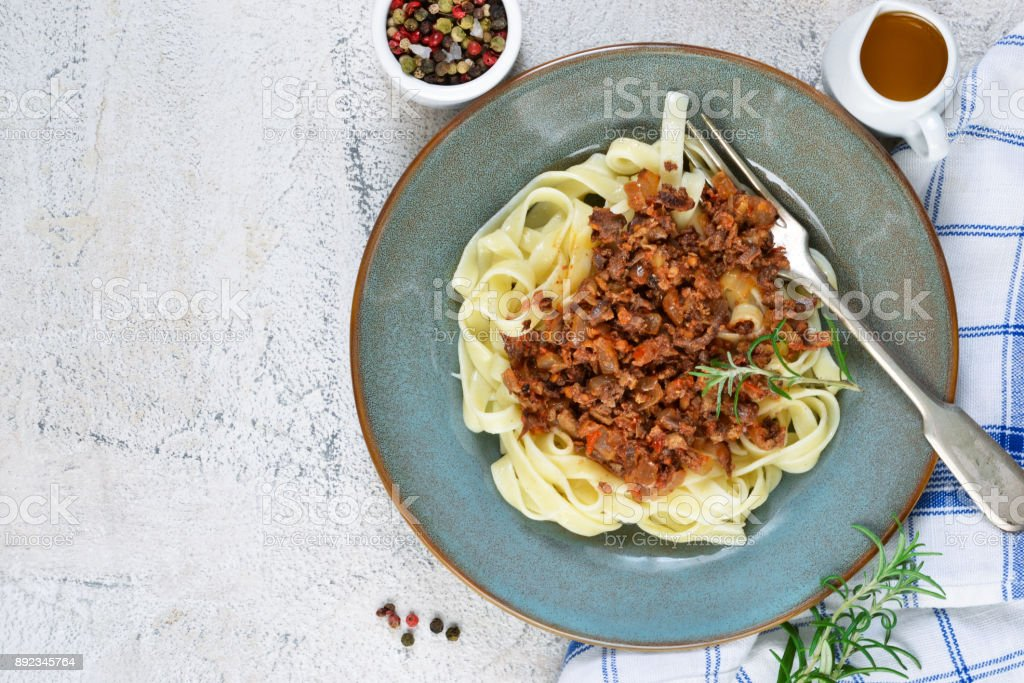 Sauce Bolognese with tagliatelle and Parmesan cheese on a concrete background. stock photo