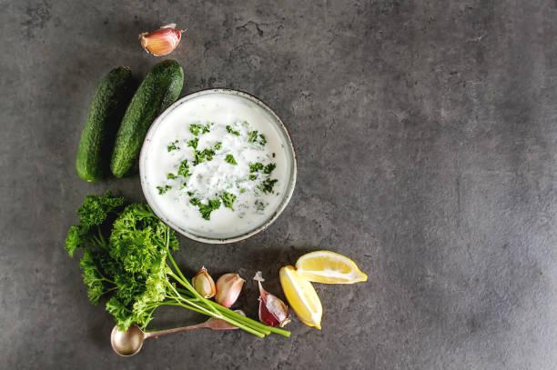 Sauce Tsatsiki with ingredients of cucumbers, garlic, parsley, lemon. Dark background. stock photo