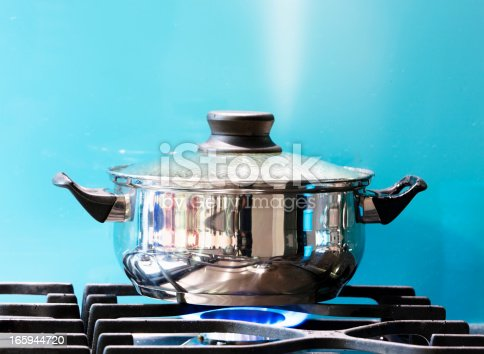 A covered pot on a lit gas burner shows a jet of steam rising as it boils against a turquoise wall.