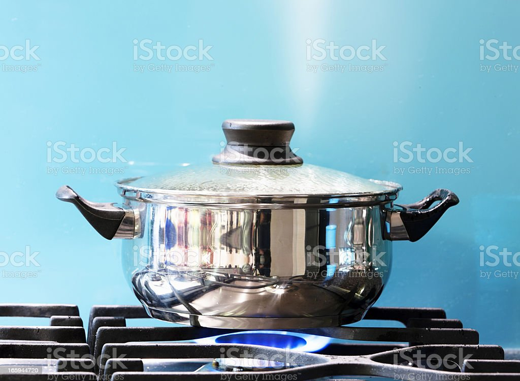 Saucepan boiling on gas stove with steam jet rising stock photo