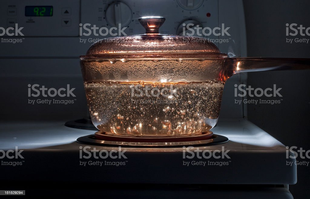 A saucepan of boiling water on a hob in a dark room stock photo