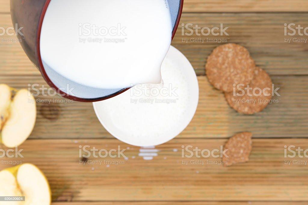 Saucepan pouring hot milk to splash in bowl to breakfast stock photo