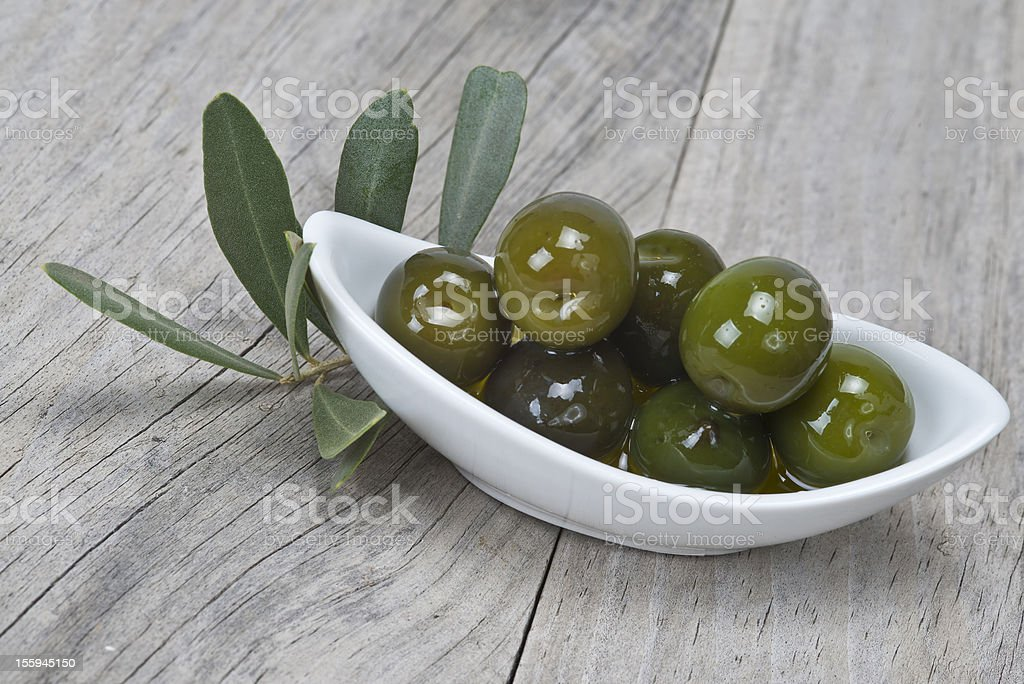 Saucer with olives on a wooden surface royalty-free stock photo