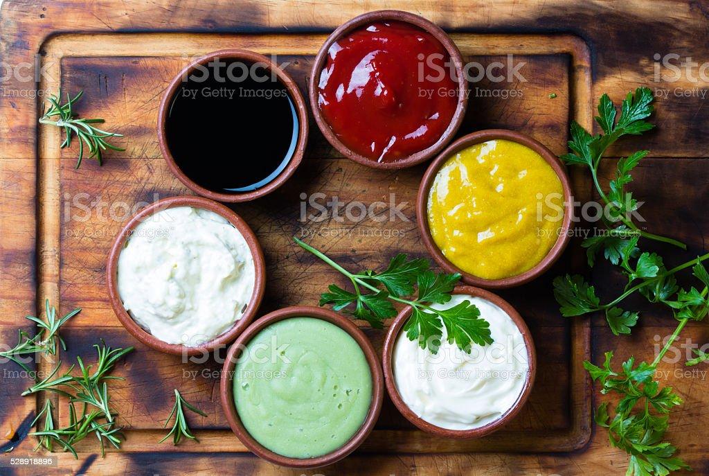 Sauces ketchup, mustar, mayonnaise, wasabi, soy sauce in clay bowls...
