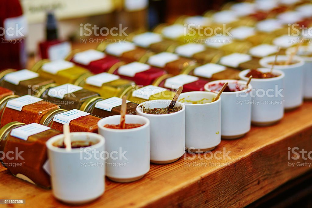 Sauces, mustards and tapenades on market Different sauces, mustards and tapenades on farmer agricultural market Basket Stock Photo