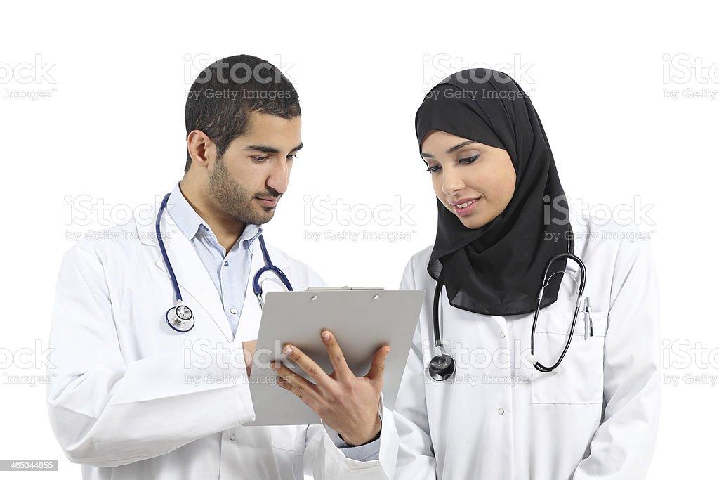 Saudi arab doctors diagnosing looking a medical history stock photo