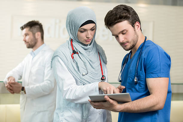 Saudi arab doctors working with a tablet. stock photo