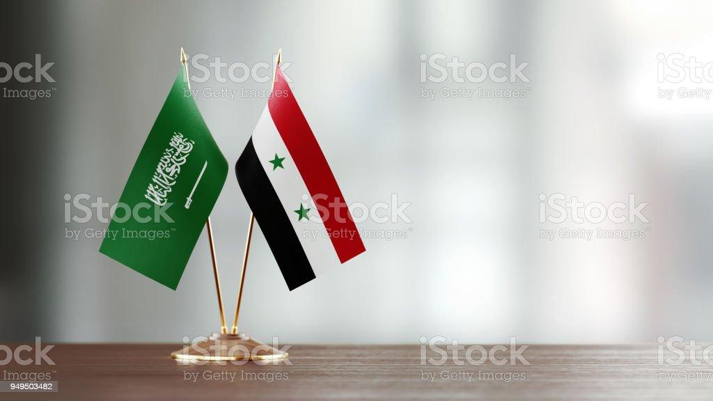 Par de la bandera de Arabia Saudita y Siria en un escritorio sobre fondo Defocused - foto de stock