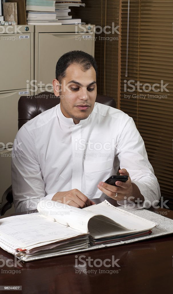 Saudi Arabian Business Man Holding Mobile Phone in Office royalty-free stock photo