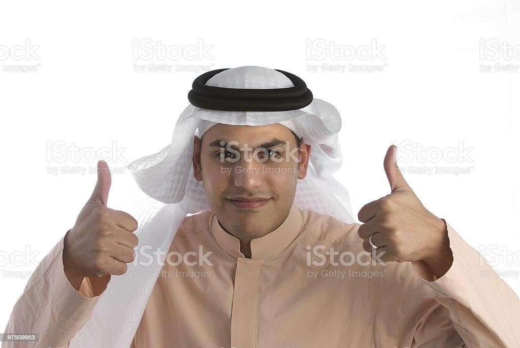 Saudi Arabian businessman smiling and giving two thumbs-up wearing thobe royalty-free stock photo