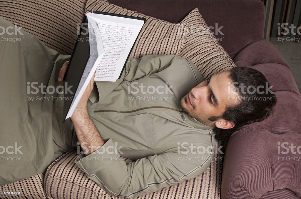 Saudi Arabian male wearing thobe and reading a book royalty-free stock photo