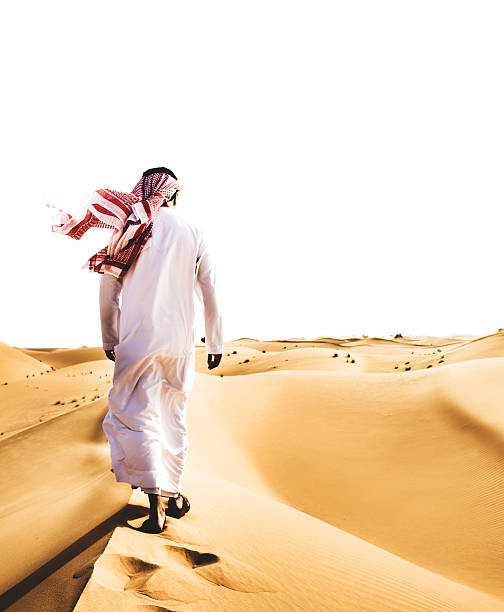 saudi arabian sheik walking on the desert - saudi national day stok fotoğraflar ve resimler