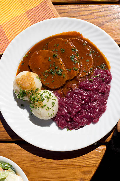 Sauerbraten with red cabbage and potatoe dumplings on plate stock photo