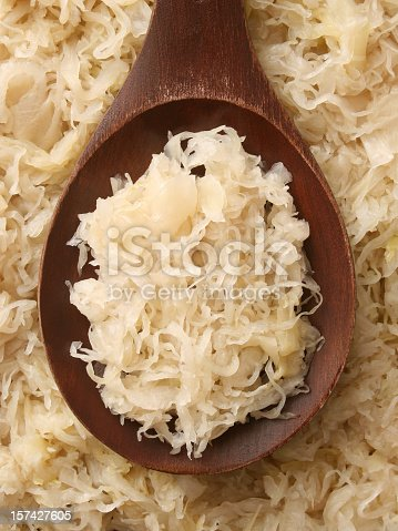 Top view of wooden spoon with some sauerkraut on it