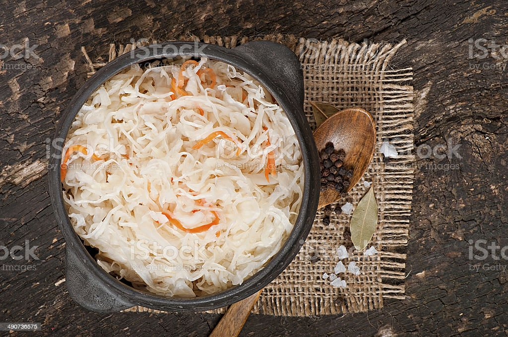 Sauerkraut with carrot in wooden bowl stock photo