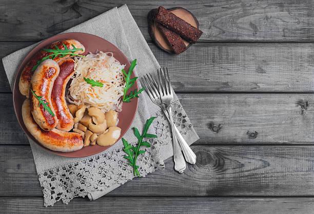 sauerkraut mit gebratenen münchen würstchen - bratwurst mit sauerkraut stock-fotos und bilder