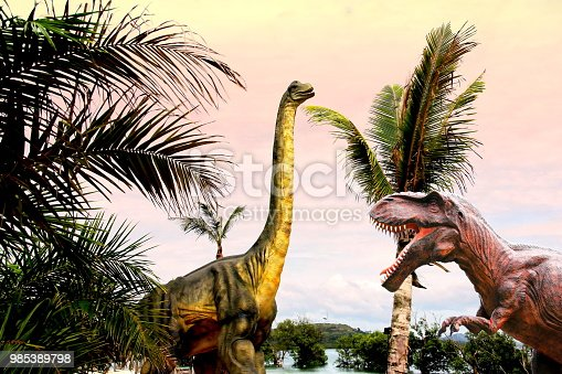 istock Sauropods and Tyrannosaurus Rex Dinosaur  on beautiful landscape background. 985389798