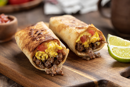 Two breakfast burritos with scrambled egg, sausage and tomato in a tortilla wrap