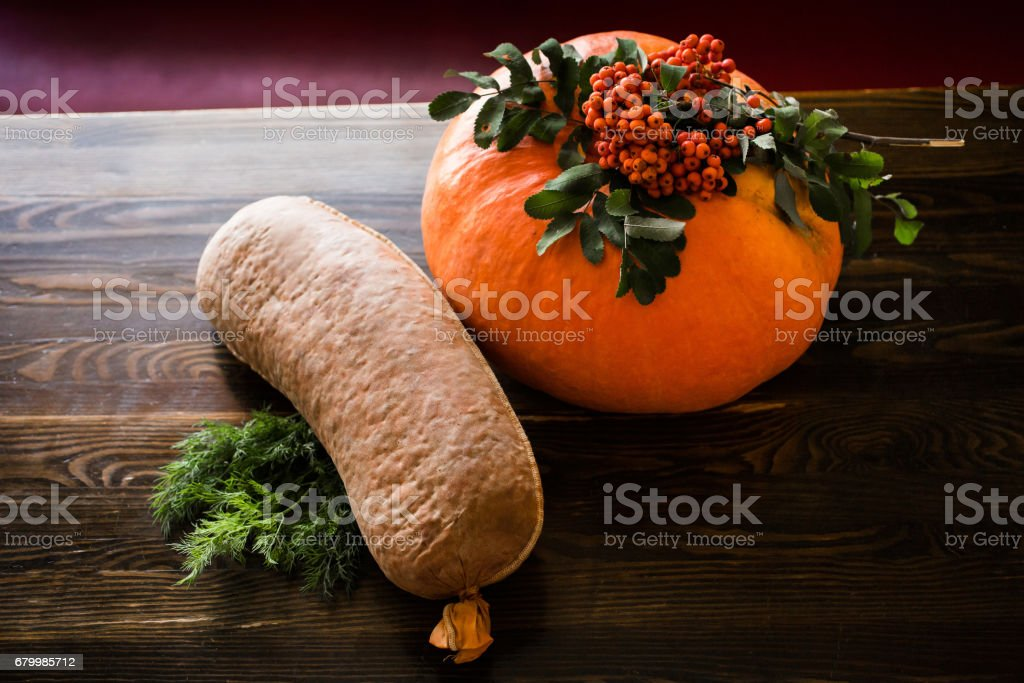 sausage and pumpkin lie on a wooden table stock photo