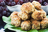For recipe request. Sausage balls on a plate with greens of spinach and grapes.