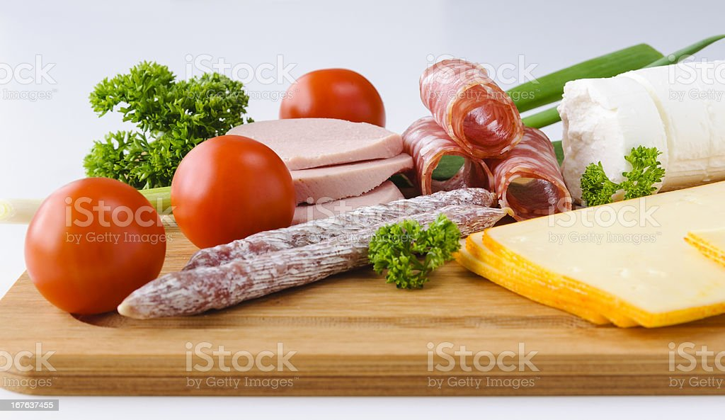 Sausage, cheese and vegetables on board royalty-free stock photo