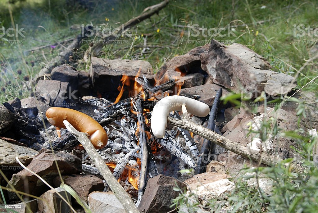 sausage on a stick over open fireplace royalty-free stock photo