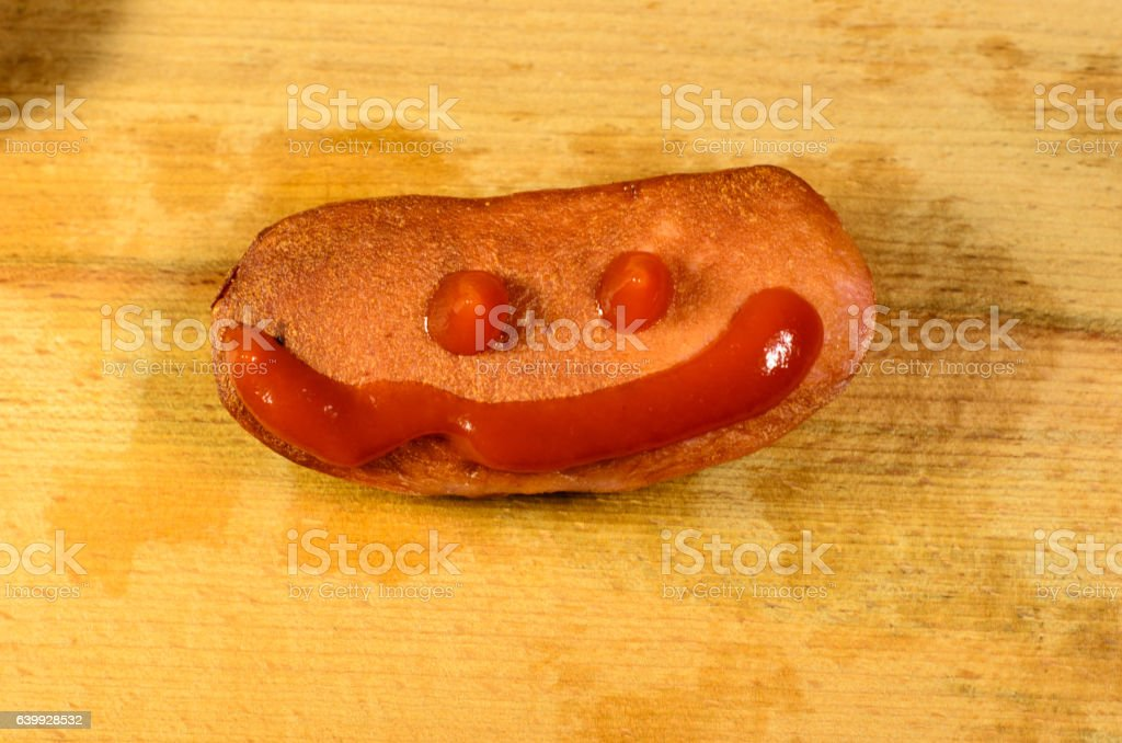 Sausage with ketchup on a wooden table stock photo