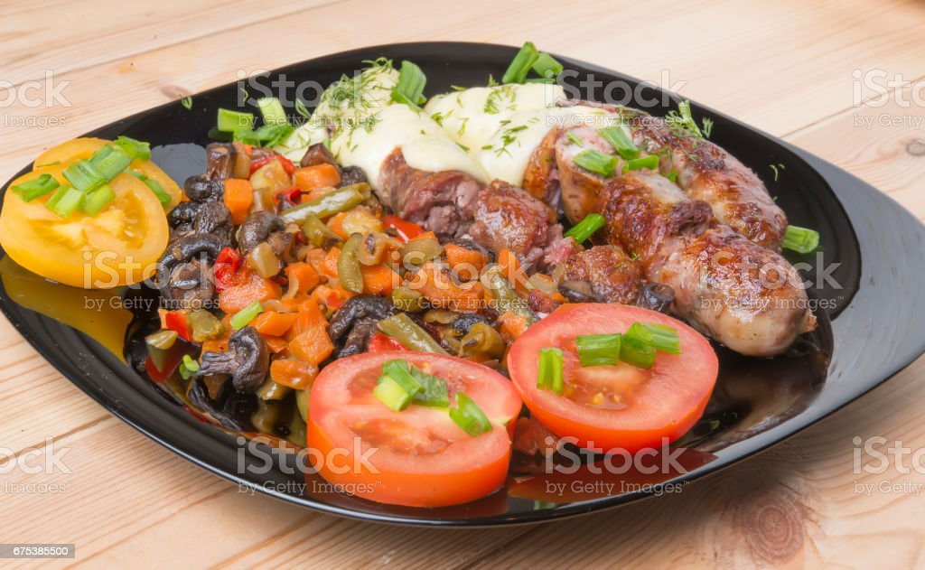 sausages fried on a grill, Baked with cheese and greens, tomatoes and onions. stock photo