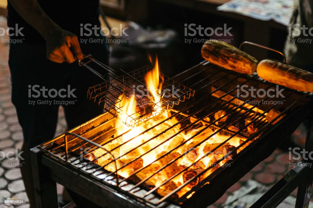 Sausages grill with burning charcoal with fire on the stove with grill on top in Bangkok, Thailand. stock photo