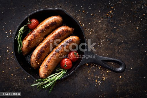 Three sausages in a cast iron skillet with seasoning