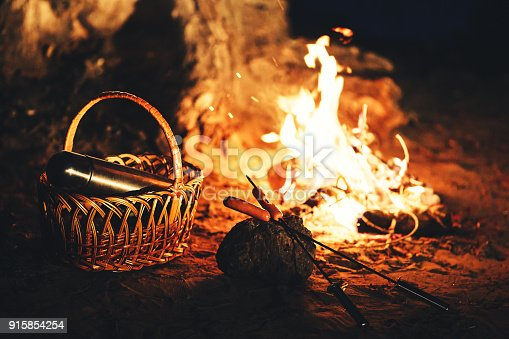 istock Sausages on skewers and a thermos in the basket against the background of the fire at night. 915854254