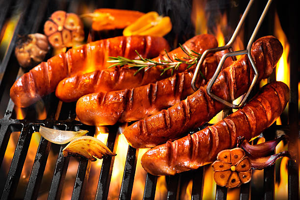 sausages on the barbecue grill with flames - sausage stock photos and pictures