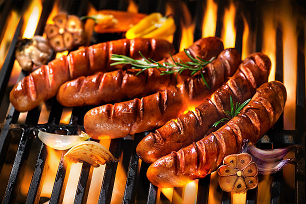 Sausages on the barbecue grill with flames stock photo