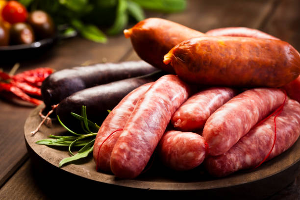 sausages variation on dark wood table - sausage stock photos and pictures